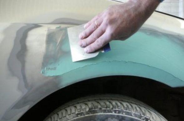 На фото - нанесение шпатлевки на автомобиль